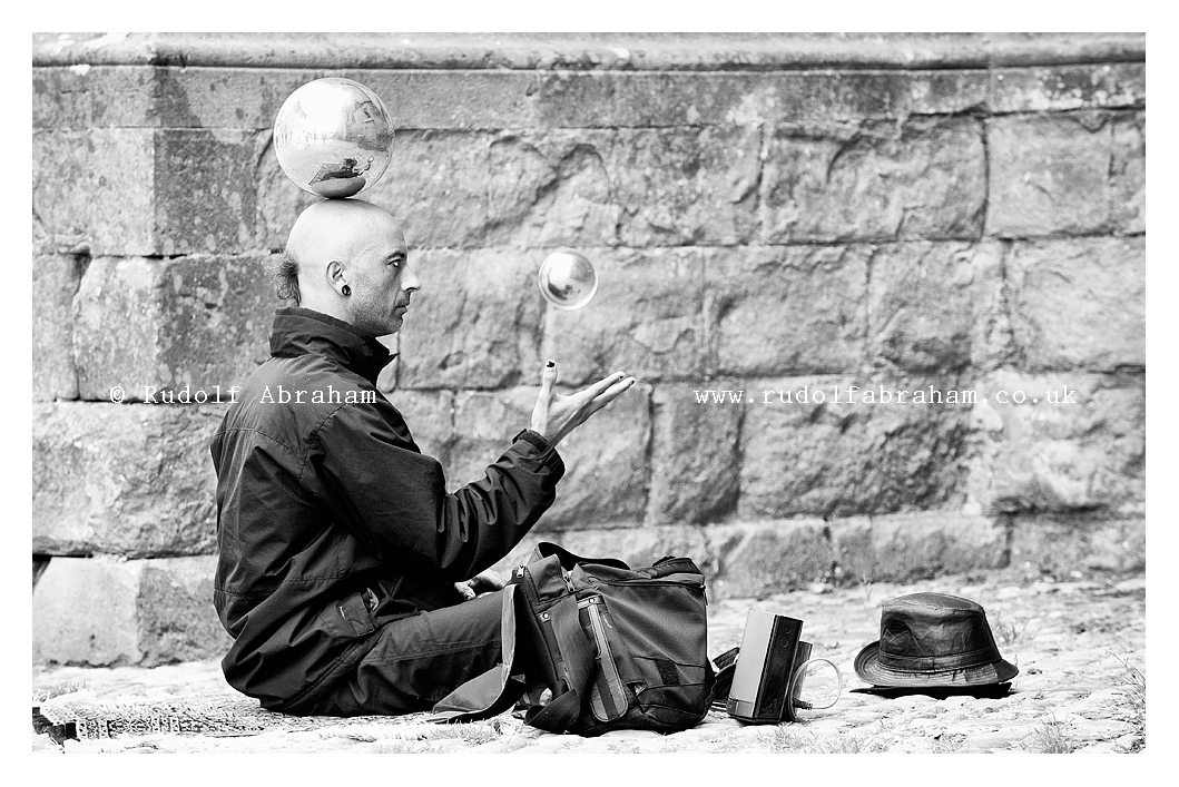 A contact juggler performs in the streets of the medieval citadel at Carcassonne, a UNESCO World Heritage Site, France. Photo © Rudolf Abraham. All rights reserved.